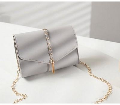 Стильная сумочка-клатч с кисточкой на цепочке серая
